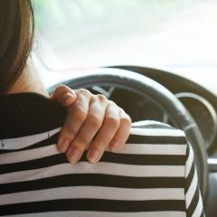 woman holding shoulder whilst driving