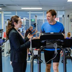 man walking on treadmill in rehabilitation clinic speaking with dr elise gane